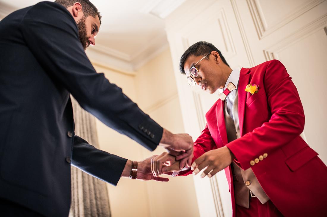 habillage du marié avec un costume de mariage rouge
