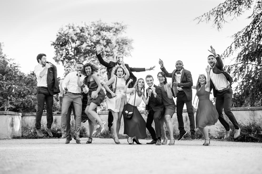 photo de groupe dynamique en noir et blanc pendant un mariage