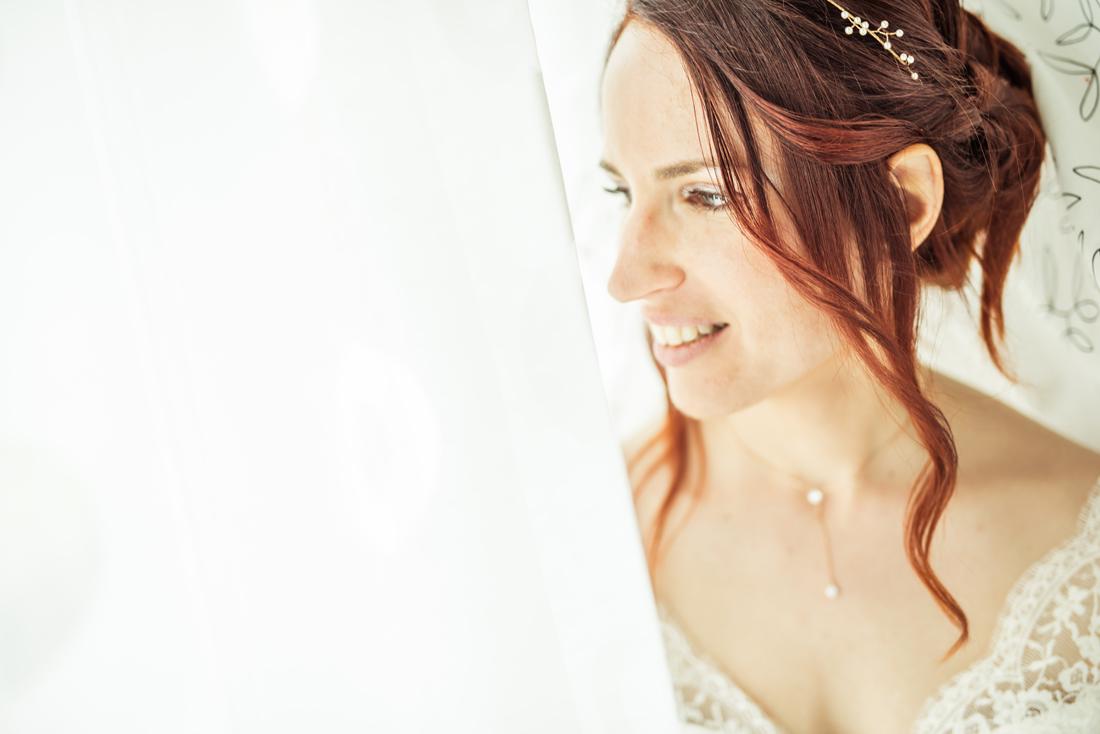 la mariée regarde de coté sur un fond blanc; elle attend.