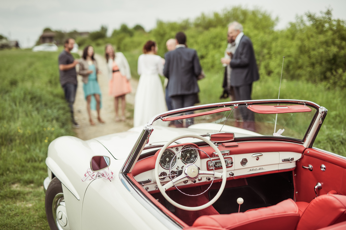 des amis se retrouvent au mariage. La photo est nette sur l'interieur d'une décapotable SL 190 mercedes et les invités sont en flous derrière.