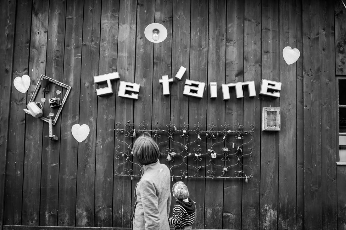 une maman et son enfant passe devant un mur en bois où est écrit je t'aime