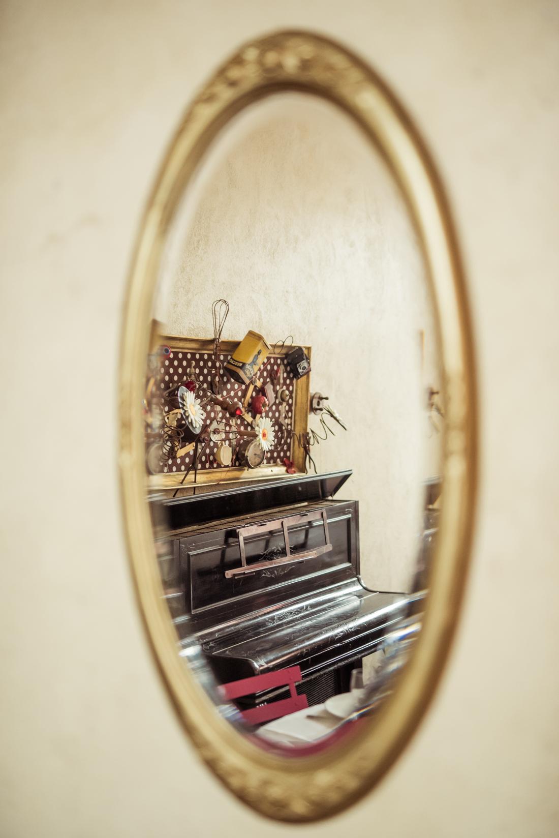 miroir avec un piano droit dans le reflet