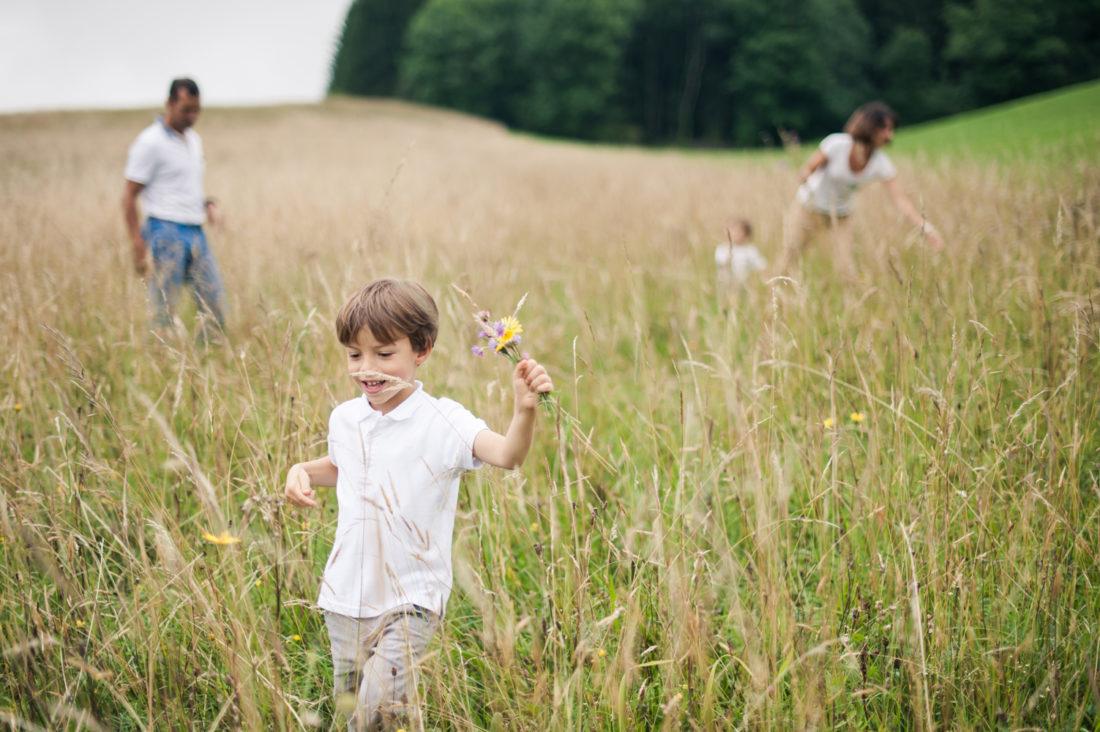 Portrait d'un enfant qui ramasse des fleurs. On voit son papa , sa maman et son petit frère en flou derrière lui.