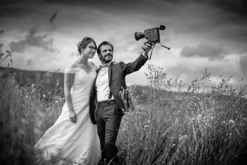 un couple de mariés se tiens dans un champs et le marié tiens une caméra super huit et se film en selfie. La photo est en noir et blanc