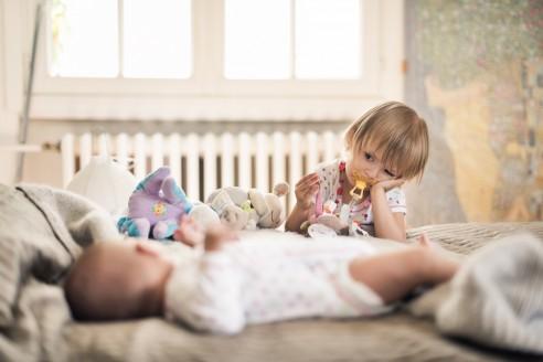 Grande soeur de 3 ans qui regarde un bébé fatiguée. Cette photo est amusante